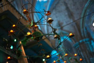 green-wire-molded-into-triangle-shaped-chandeliers-with-votives