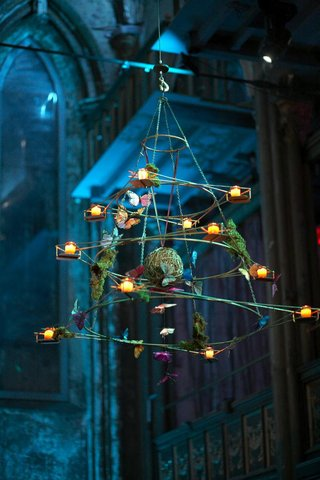 twisted-triangle-shaped-wire-hanging-from-ceiling-decorated-with-votives-and-silk-butterflies