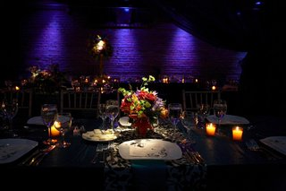 table-lit-by-purple-lighting-with-jewel-toned-flowers-and-candles