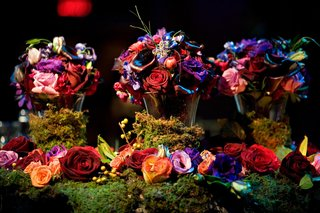brass-vases-covered-in-moss-topped-with-jewel-toned-flowers