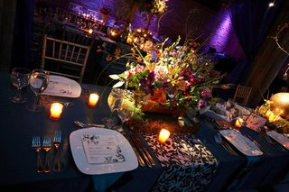 floral-centerpiece-on-table-with-blue-linens-and-candles