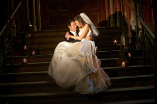 groom-holds-bride-wearing-ball-gown-on-staircase