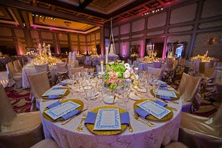 ballroom-wedding-with-gold-charger-plate-blue-napkin-low-centerpiece-chair-covers
