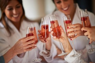 bridesmaid-in-white-robes-with-tall-champagne-flutes-and-raspberry-fruits