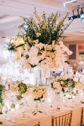 wedding-reception-gold-chairs-white-antique-linens-low-centerpieces-candelabra-around-tall-flowers