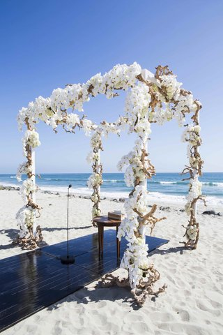 wedding-canopy-constructed-of-driftwood-and-orchids