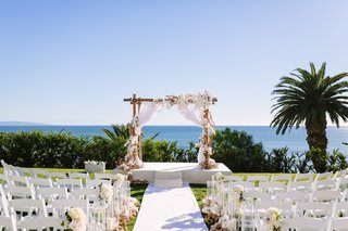 wooden-arbor-with-white-fabric-orchids-and-roses-ocean-views-bel-air-bay-club