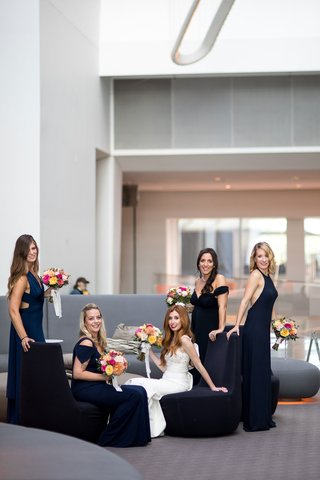 bride-in-dress-from-mark-ingram-atelier-in-hotel-lobby-with-bridesmaids-in-navy-dresses-mismatched