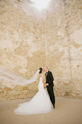 bride-in-strapless-romona-keveza-wedding-dress-kissing-groom-at-mission