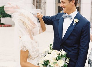 bride-in-carolina-herrera-wedding-dress-ivory-green-bouquet-with-veil-over-face-and-groom-smiling