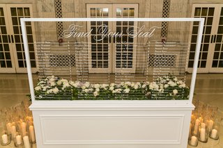 clear-wedding-sign-seating-chart-white-calligraphy-candles-in-hurricane-vases