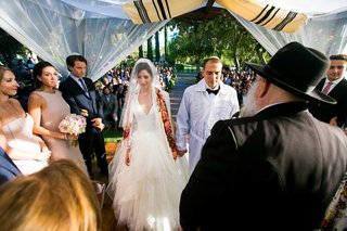 a-jewish-couple-wearing-traditional-garb-marrying-under-chuppah