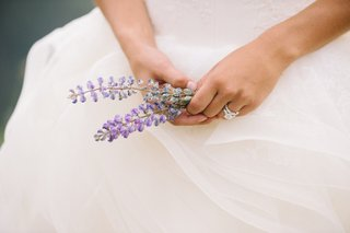 bride-holding-purple-flora-in-hands-against-skirt