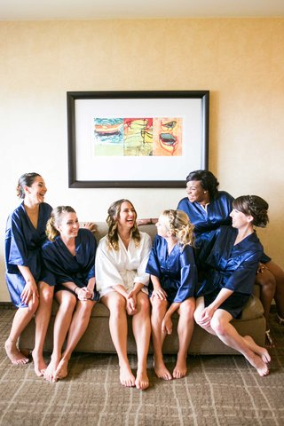 bride-in-white-robe-bridesmaids-in-navy-robes-laughing