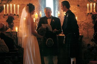 bride-and-groom-at-altar-in-stone-candlelit-castle-room