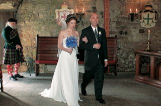 bride-walks-down-aisle-with-father-in-stone-castle-room