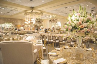 wedding-reception-with-round-table-gold-sequined-tablecloth-chairs-love-seats-peach-pink-roses