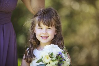 flower-girl-in-white-sleveless-dress-carries-bridesmaids-bouquet-of-white-and-purple-flowers