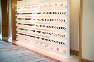 ballroom-wedding-pink-decor-black-white-hockey-puck-escort-cards-on-shelves