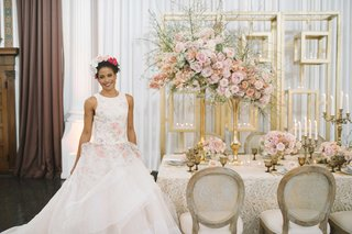 bride-in-floral-ball-gown-next-to-taupe-champagne-tablescape-pink-centerpieces-gold-candelabra