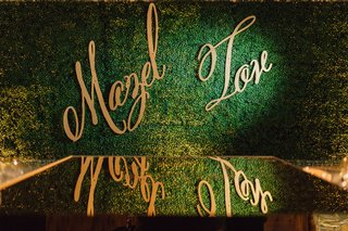 wedding-signage-mazel-tov-modern-calligraphy-gold-on-green-hedge-wall-mirror-floor