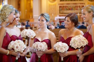 bridesmaids-in-red-dresses-hold-bouquets-of-light-purple-roses-in-church