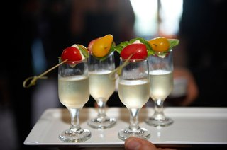 glasses-of-champagne-are-served-with-caprese-salad-hors-doeuvres-at-wedding-cocktail-hour