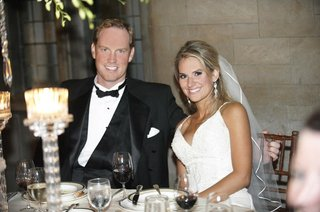 bride-in-a-spaghetti-strap-gown-sits-with-groom-in-black-tuxedo-at-reception