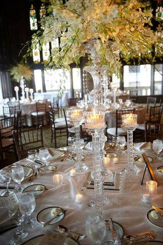 wedding-reception-table-with-tall-crystal-candle-holders-and-vase-with-white-flowers