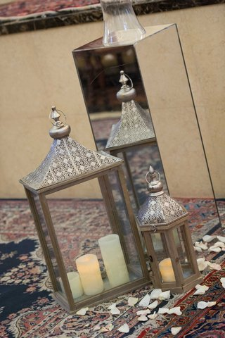 moroccan-lantern-on-persian-rug-with-rose-petals-and-candles-next-to-mirror-riser-at-church-ceremony