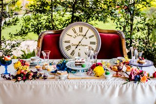 alice-in-wonderland-inspired-wedding-styled-shoot-clock-on-velvet-couch-sweetheart-table