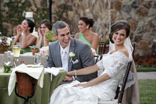 bride-and-groom-at-sweetheart-table-laugh-with-guests
