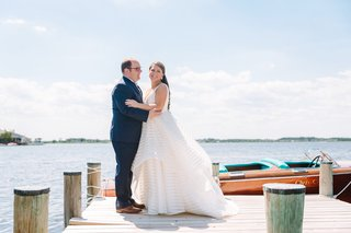 bride-in-striped-hayley-paige-wedding-gown-with-groom-in-navy-on-the-private-dock