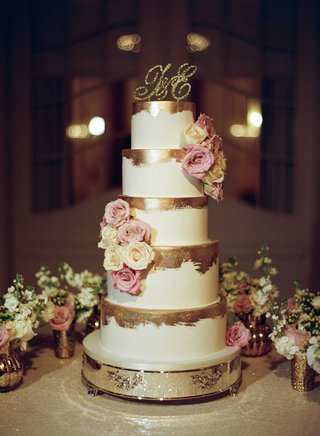 tall-white-wedding-cake-with-gold-brush-strokes-on-top-and-fresh-pink-white-roses-gold-monogram