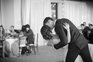 black-and-white-photo-of-groom-dips-bride-for-a-kiss-during-first-dance