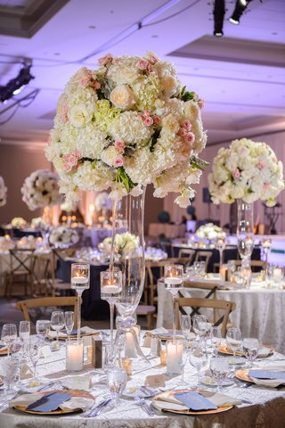 round-table-blue-and-gold-place-setting-white-blush-hydrangea-rose-tall-centerpiece-floating-candles
