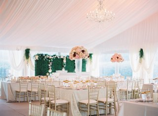 wedding-reception-green-hedge-wall-flowers-tall-centerpieces-gold-chairs-reception-decor-ideas