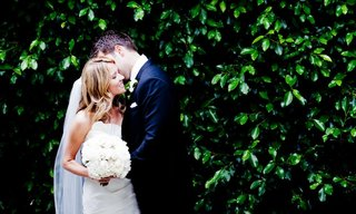bride-and-groom-in-front-of-hedge-at-wedding