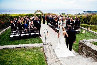 bride-walks-down-aisle-with-dad-on-oceanfront-lawn