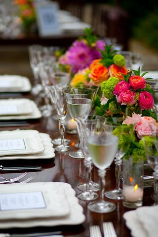 long-reception-table-with-bright-pink-flowers-in-vases
