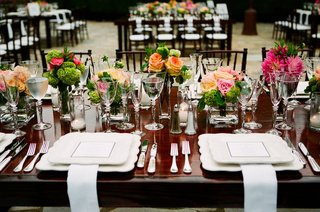 wood-table-with-bright-flowers-and-scalloped-chargers