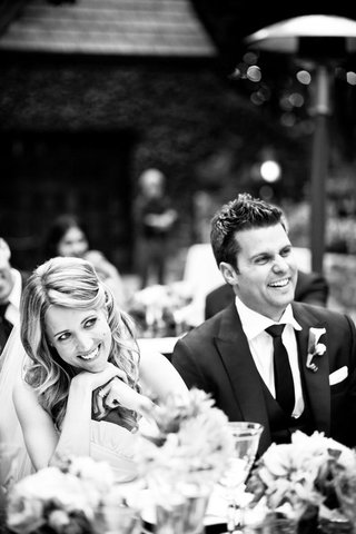 black-and-white-photo-of-bride-and-groom-smile-at-guests-during-wedding-toasts