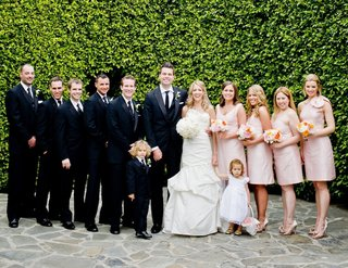 bride-and-groom-in-front-of-hedge-with-bridesmaids-and-groomsmen