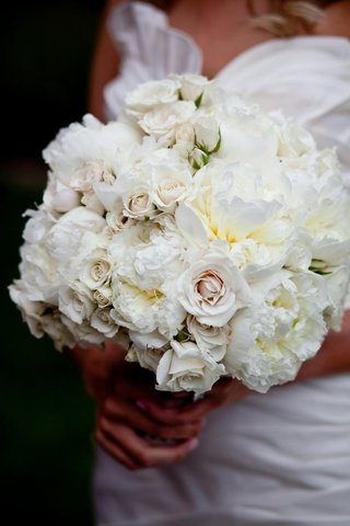 bride-holding-white-wedding-bouquet-with-peonies-and-roses