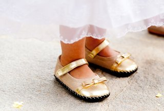 moccasin-style-gold-shoes-with-ankle-strap-and-bow