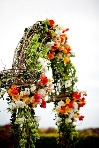 greenery-branches-and-bright-roses-on-wedding-flower-arch
