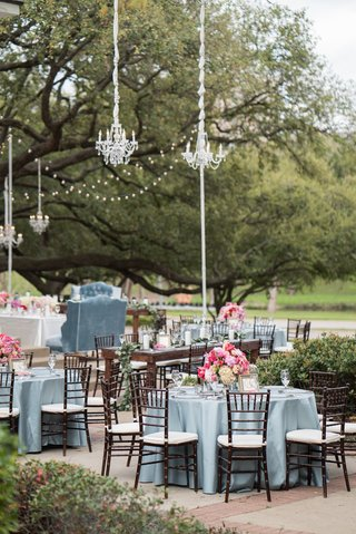 chandeliers-hanging-from-trees-for-outdoor-reception-blue-linens-chiavari-chairs