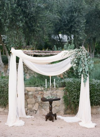 rustic-wedding-ceremony-structure-with-white-fabric-and-green-leaves-for-outdoor-wedding-ceremony