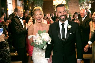 bride-in-off-the-shoulder-wedding-dress-and-bouquet-holding-hands-with-new-husband-adam-touni