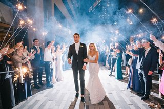 bride-and-groom-hold-each-other-as-they-walk-through-pathway-created-by-guests-sparklers-night